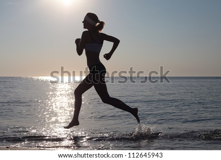 Beautiful young sport woman running on beach on sunny summer day - stock photo