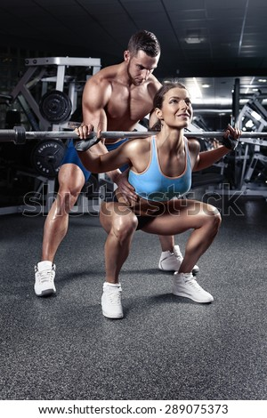 beautiful young sporty sexy couple doing squat workout in gym - stock photo