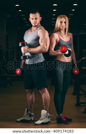 beautiful young sporty sexy couple showing muscle and workout in gym dumbbell - stock photo