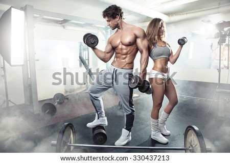 beautiful young sporty sexy couple showing muscle and workout in gym during photoshooting - stock photo