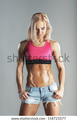 beautiful young sporty woman looking on her abs - stock photo