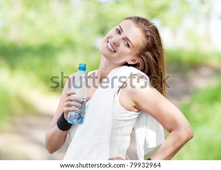 beautiful young  sporty woman running in the park on a warm summer day and drinking water - stock photo