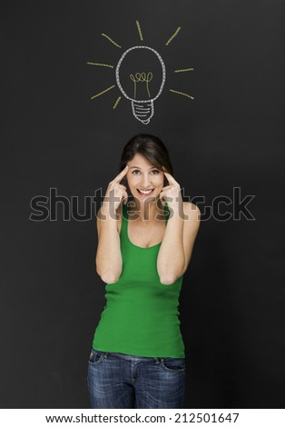 Beautiful young student having an idea, with lamp bulb designed on a chalkboard - stock photo