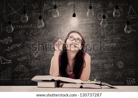Beautiful young student is looking at bright lit lamp with written blackboard behind her - stock photo