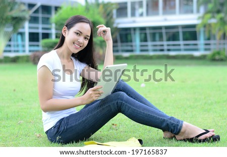 Beautiful young student relaxing on green grass with computer tablet - stock photo