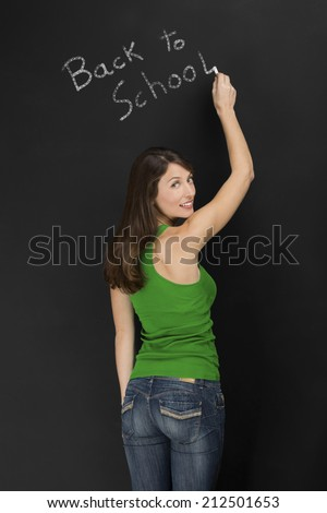 Beautiful young student writing on chalkboard the words back to school - stock photo