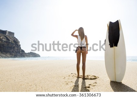 Beautiful young surfer girl getting ready to surf - stock photo