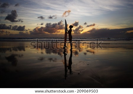 Beautiful young surfer girl in bikini with surfboard on a beach  - stock photo