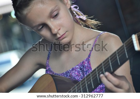 Beautiful young teenage girl playing acoustic guitar in the street - stock photo