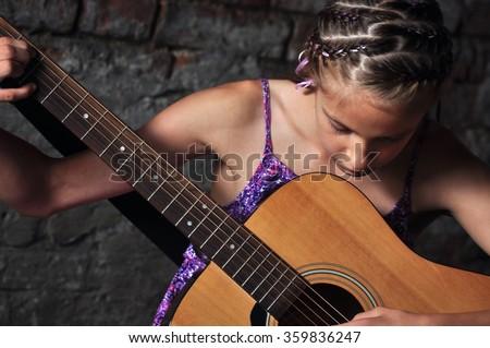 Beautiful young teenage girl plays musical instrument guitar.  - stock photo