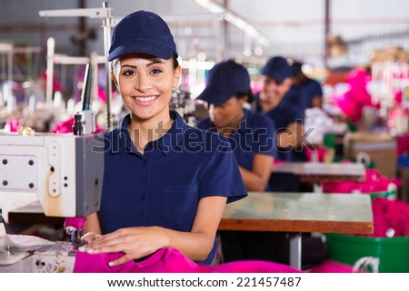 beautiful young textile machinist using sewing machine in clothing factory - stock photo