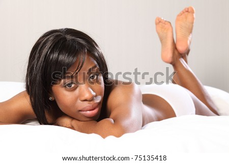 Beautiful young topless African American woman lying casually in bed, very relaxed with chin resting on her hands. - stock photo