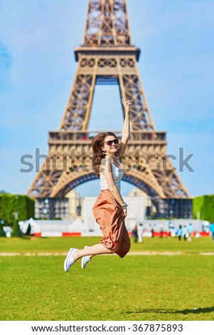 Beautiful young tourist or student girl in Paris jumping near the Eiffel tower on a summer day - stock photo