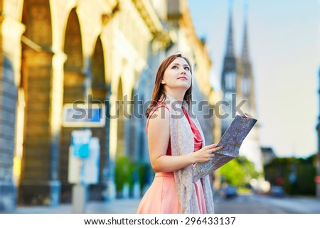 Beautiful young tourist using map in the street in Vienna, Austria - stock photo