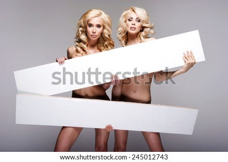 Beautiful young two women holding empty white board  - stock photo