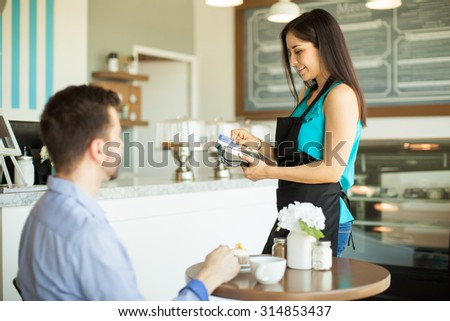Beautiful young waitress swiping a credit card from a customer in a bank terminal - stock photo