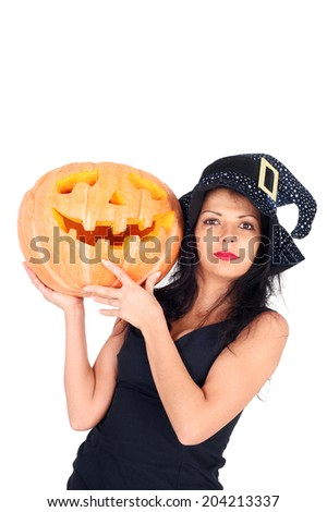 beautiful young witch with the Halloween pumpkin - stock photo