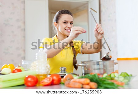 beautiful young woman adds spice or salt in saucepan at kitchen - stock photo