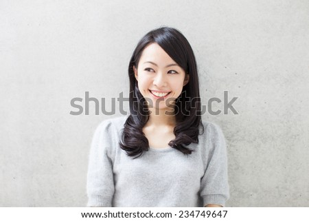beautiful young woman against concrete wall - stock photo