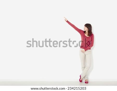 Beautiful young woman  against to a white wall pointing to the right side with copyspace - stock photo
