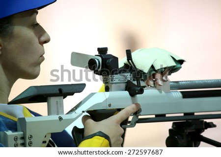 beautiful young woman aiming a pneumatic air rifle - stock photo