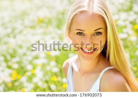 Beautiful young woman among dandelions - stock photo