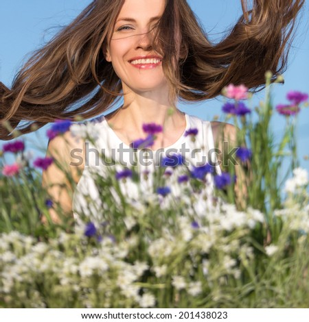 Beautiful young woman among flowers with flying blowing hair enjoying her summer holiday.motion. focus on woman - stock photo