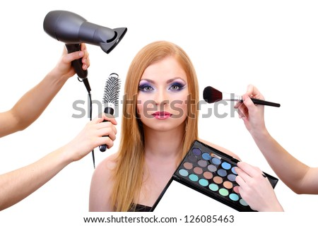 Beautiful young woman and hands with eyes shadows, brush and hairdryer, isolated on white - stock photo