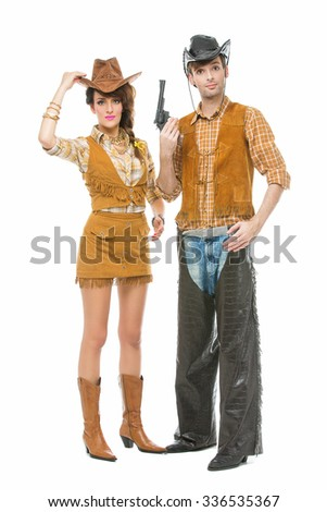 Beautiful young woman and handsome man looking like dolls dressed in cowboy costumes. Isolated over white background. Copy space. - stock photo