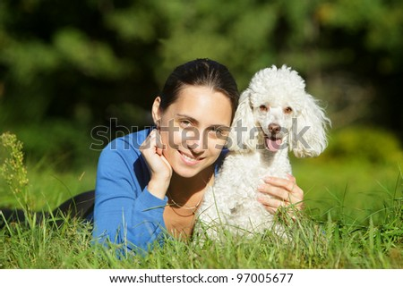 Beautiful young woman and happy white dog resting on green lawn - stock photo