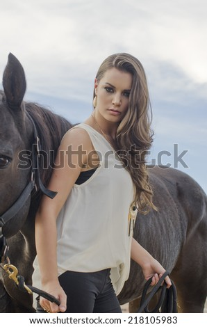 Beautiful young woman and her horse - stock photo