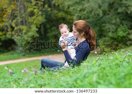 Beautiful young woman and her little bay relaxing in the garden - stock photo