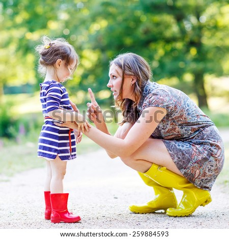 Beautiful young woman and her little cute kid daughter in yellow and red rubber rainboots, family look in summer park. Active leisure with kids. - stock photo