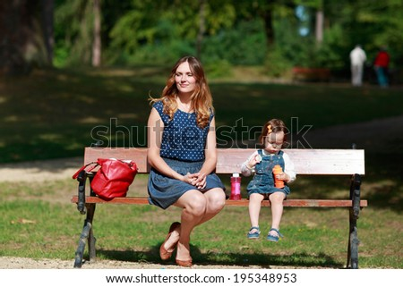 Beautiful young woman and little girl sitting on bench in summer park, outdoors. - stock photo