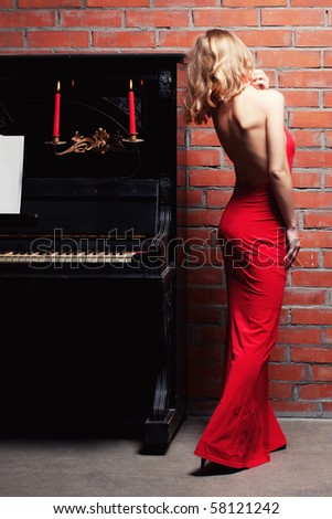 beautiful young woman and piano - stock photo