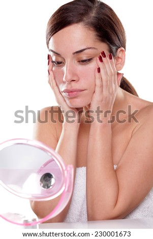 Beautiful young woman apply face cream - stock photo