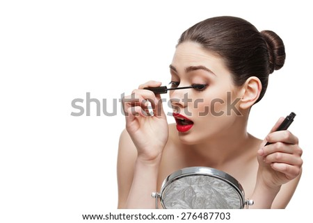 Beautiful young woman applying black mascara looking at table mirror. Isolated over white background. Copy space. - stock photo