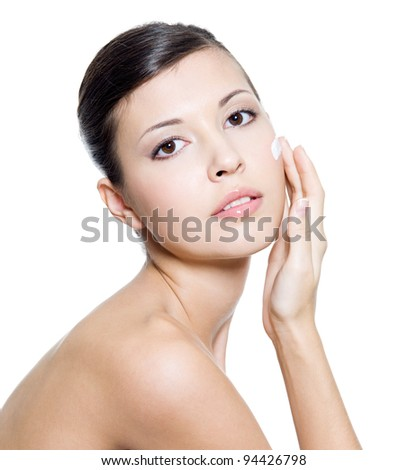 Beautiful young  woman applying cosmetic  cream around the eye . Isolated on white background - stock photo