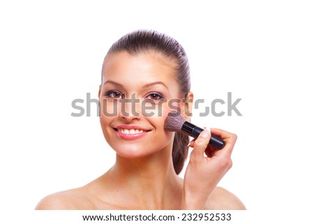 Beautiful young woman applying cosmetic paint brush - stock photo