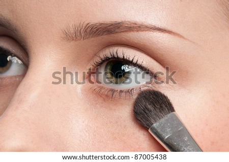 Beautiful young woman applying cosmetic paint brush - close-up portrait of eye shadow zone - stock photo