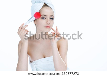 Beautiful young woman applying foundation on her face with tassel, skin care concept / photo composition of blonde girl in towel - isolated on white background - stock photo