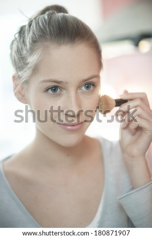 beautiful young woman applying makeup before her mirror - stock photo