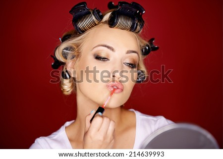 Beautiful young woman applying makeup with her blond hair in curlers as she carefully applies lipstick while looking in a mirror - stock photo