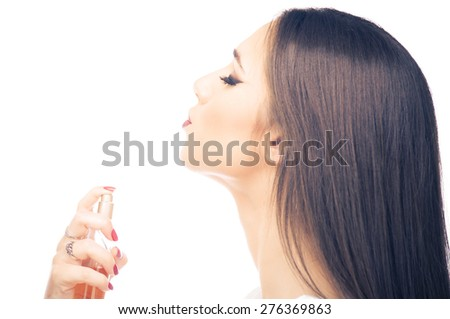 Beautiful young woman applying perfume on her neck - stock photo