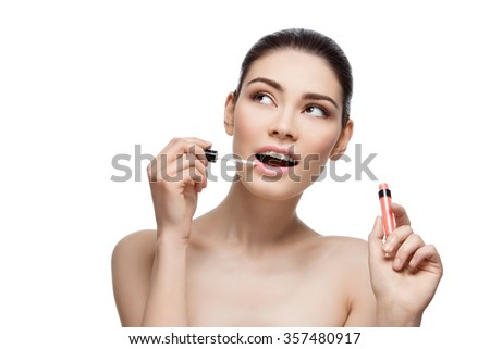 Beautiful young woman applying pink lipgloss to lips. Isolated over white background. Copy space. - stock photo