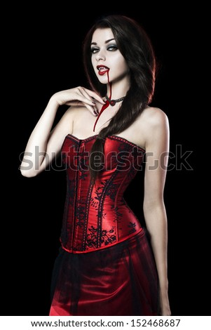 Beautiful Young woman as sexy vampire in red dress - halloween portrait - stock photo