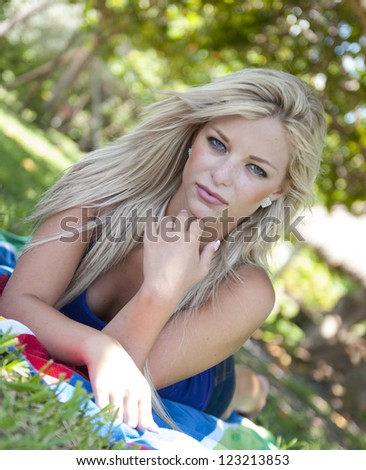Beautiful young woman at a park - stock photo