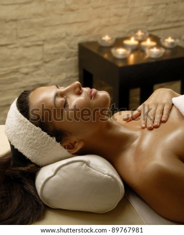 Beautiful young woman at beauty salon spa getting a body treatment. - stock photo