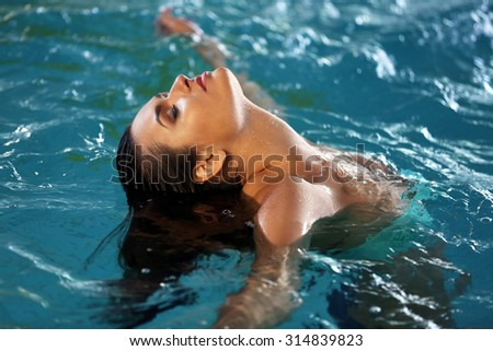 Beautiful young woman at swimming pool - stock photo