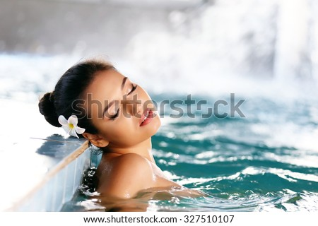 Beautiful young woman at swimming pool - stock photo